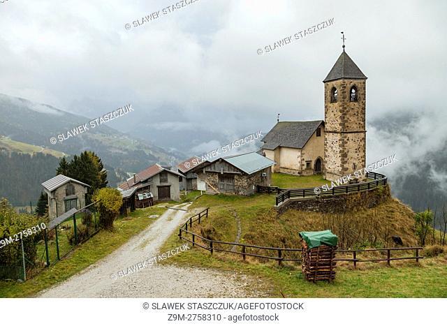 Misty autumn day at the 16th century church of St Lorenzo near Candide, Belluno province, Veneto, Italy. Dolomites