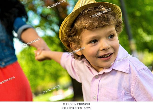 Close up of boy holding mother's hand in park