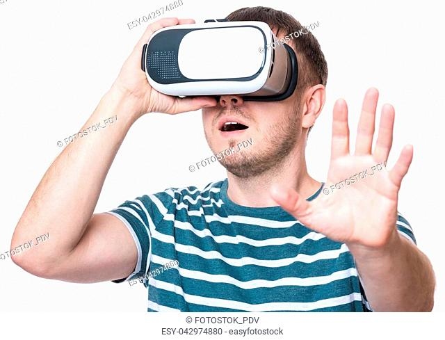 Amazed man wearing virtual reality goggles watching movies or playing video games gesticulating hands, isolated on white background