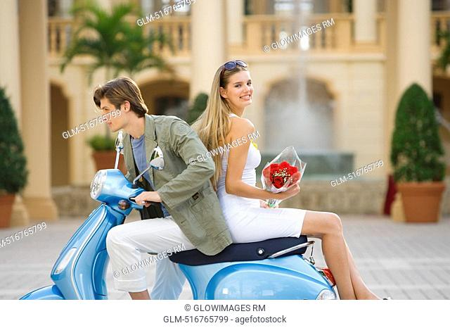 Couple sitting on a moped, Biltmore Hotel, Coral Gables, Florida, USA