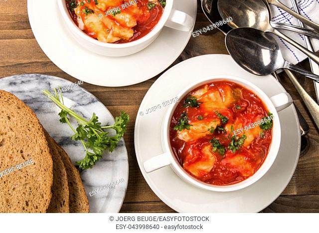 fish soup in a bowl and parsley with home baked sliced bread