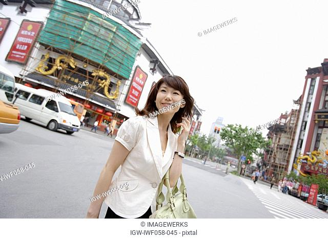 Young woman carrying shoulder bag, smiling