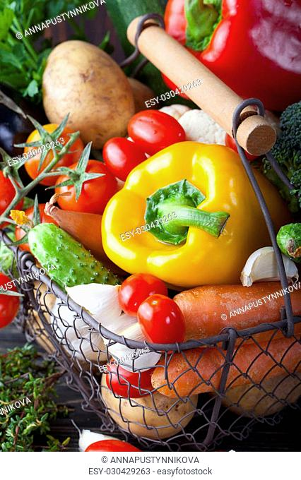 Vegetables variety in a wire basket on a wooden background. Copy space