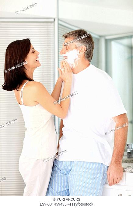 Portrait of a beautiful lady applying shaving cream on her husbands face