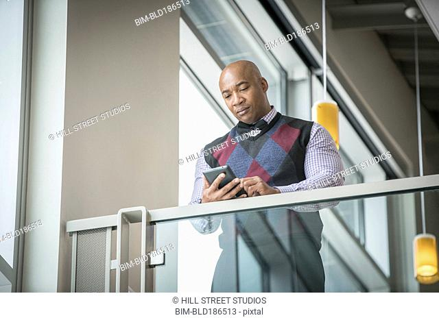 Black businessman using cell phone at balcony
