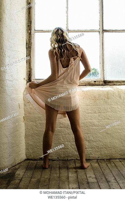 Young woman in pink gawn by the window