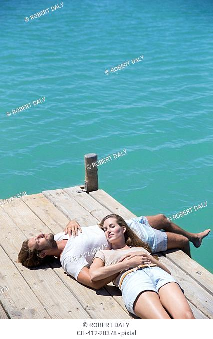 Couple relaxing together on wooden dock