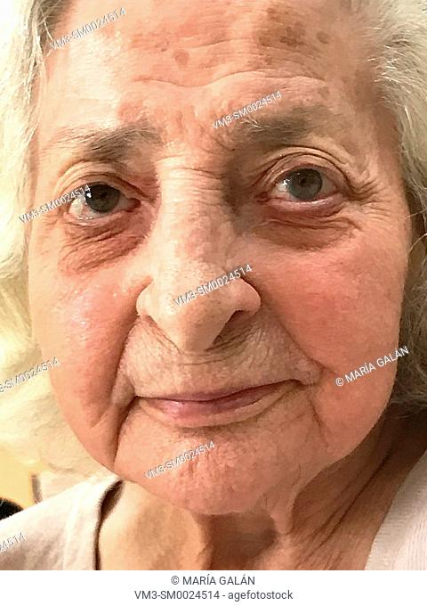 Portrait of lovely old woman smiling. Close view