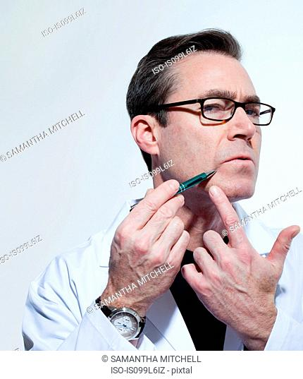 Plastic surgeon using pen to point to his face