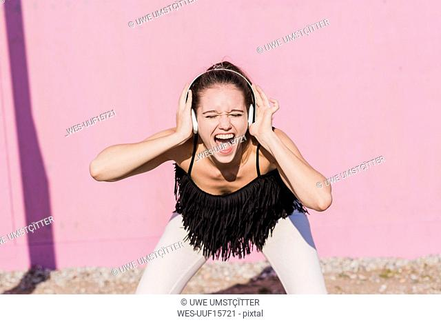 Exuberant young woman wearing headphones screaming in front of pink wall