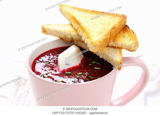cup of beetroot cream soup with toast on white table mat - close up