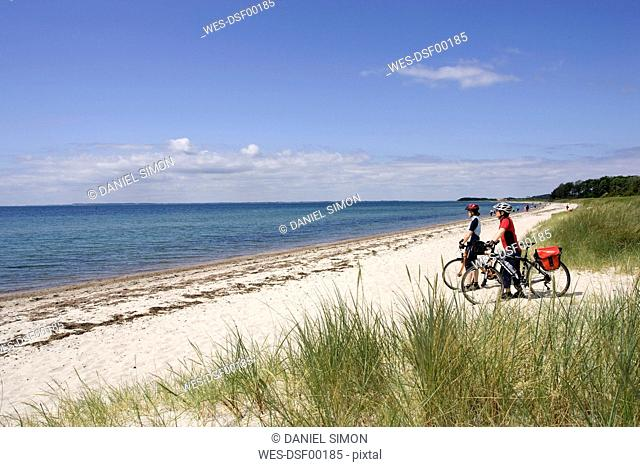 Denmark, Fuenen, Mountainbikers taking a break on the coast