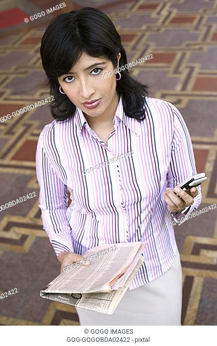 Businesswoman carrying newspaper and cell phone