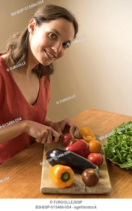 Young woman slicing vegetables