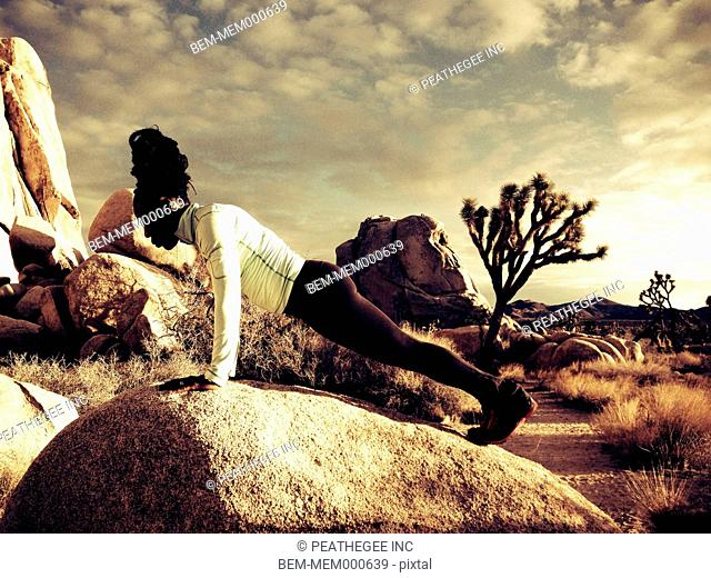 Woman doing push ups in Joshua Tree National Park, California, United States