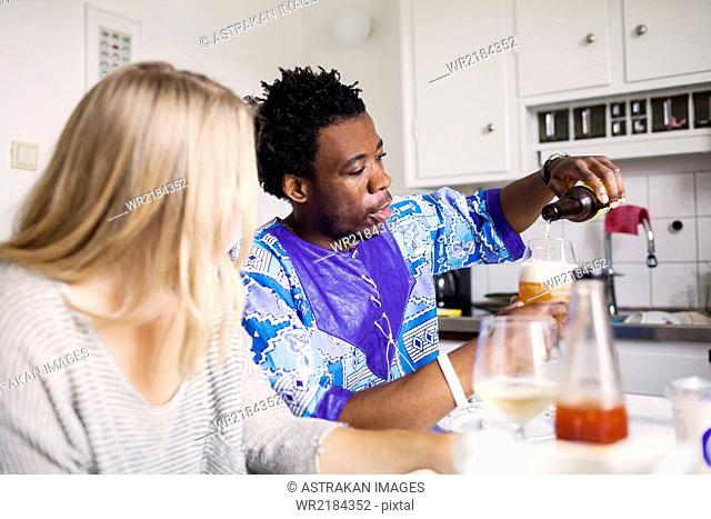 Young woman looking at friend pouring beer in glass at home