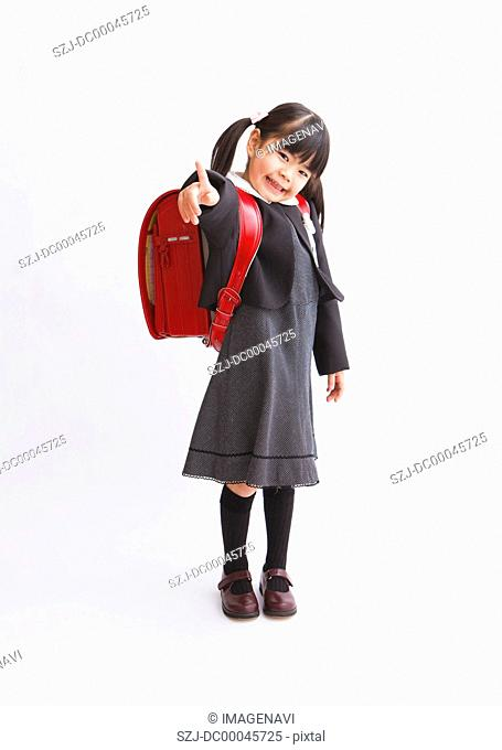 Girl with school bag pointing
