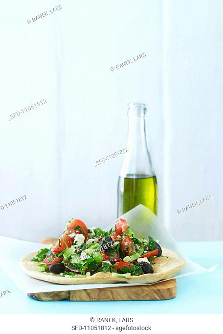 Greek salad on unleavened bread with a bottle of olive oil in the background