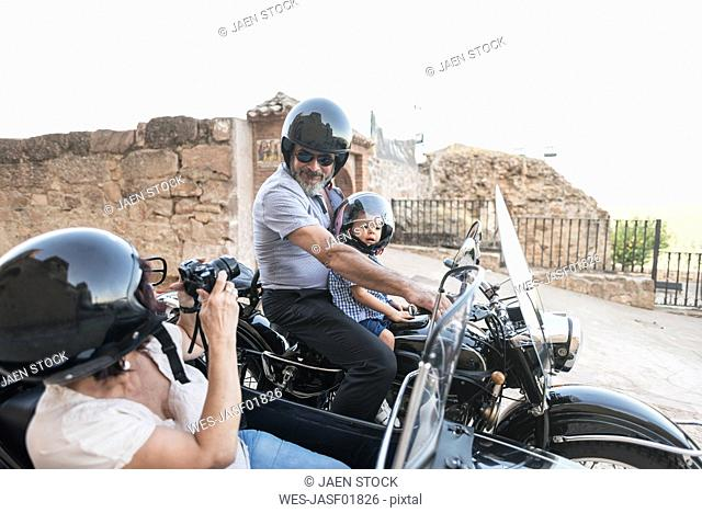 Spain, Jaen, woman taking picture of grandfather and grandson on motorcycle with a sidecar