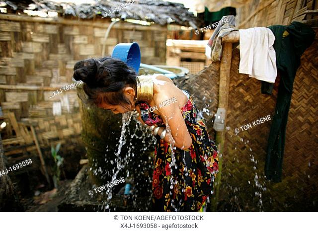 A Longneck girl splashes herself with water Approximately 300 Burmese refugees in Thailand are members of the indigenous group known as the Longnecks The...