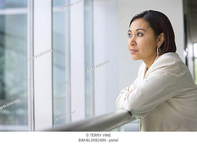 Hispanic businesswoman leaning against railing