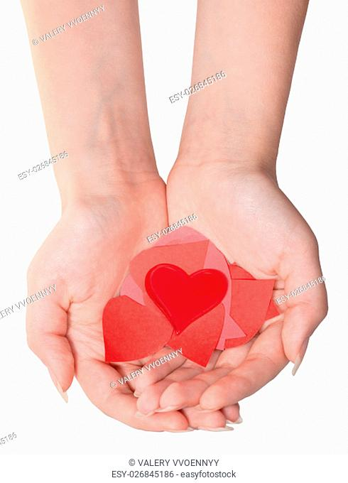 glass heart above pile of paper hearts on female palms isolated on white background