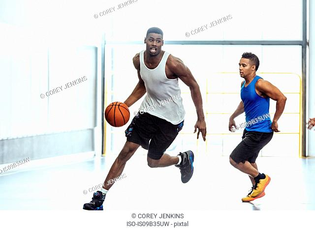 Male basketball players running with ball and defending on basketball court