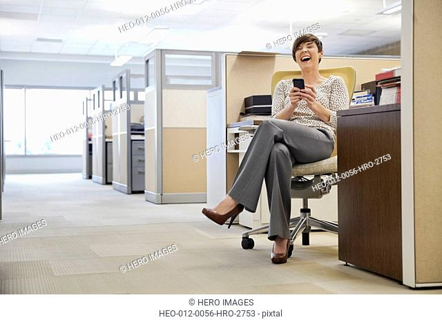 Laughing businesswoman text messaging on mobile phone in office