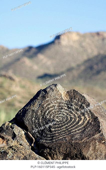 Rock art at Signal Hill, created by the Hohokam Indians, showing spiral petroglyph with the Tucson Mountains in the background, Saguaro National Park, Arizona