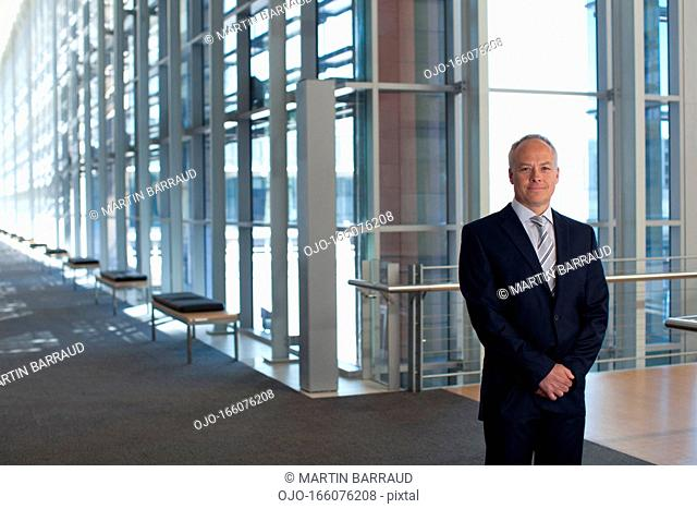 Businessman at window in office lobby