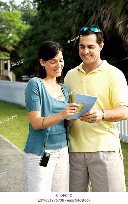 Mid-adult Caucasian couple holding map and smiling