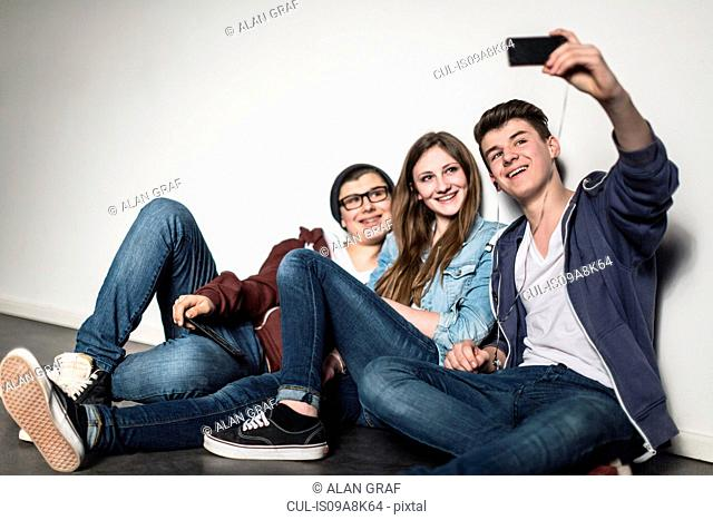 Three teenagers taking self portrait photograph using smartphone