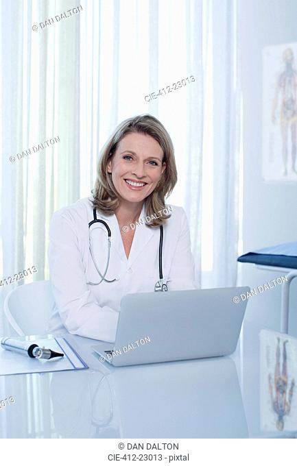 Portrait of smiling female doctor sitting at desk with laptop