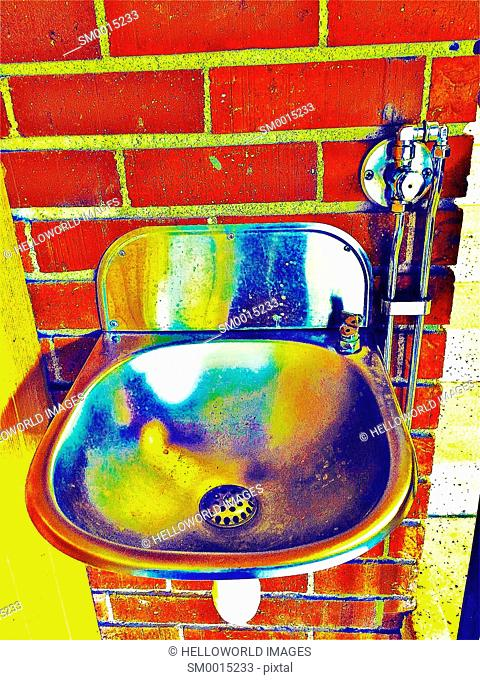 Metal water drinking fountain on tiled wall