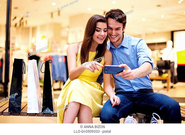 Smiling young couple looking at mobile phone Debica, Poland