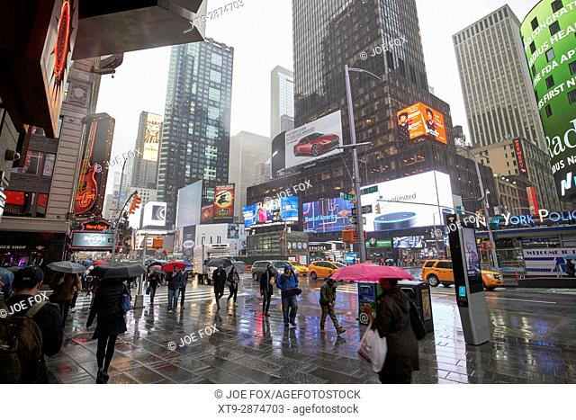 people holding umbrellas walk through wet times square during rain shower midtown New York City USA