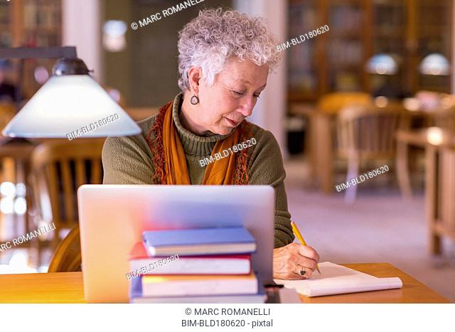 Older mixed race woman using laptop in library