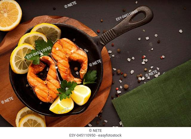 Fried or grilled salmon fillet on cast-iron pan with
