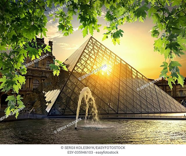 PARIS, FRANCE - AUGUST 30, 2016: Glass pyramid of Louvre among the leaves of a maple at sunrise