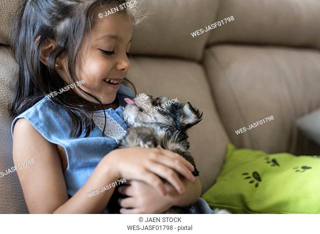 Happy little girl sitting on the couch with puppy on her lap