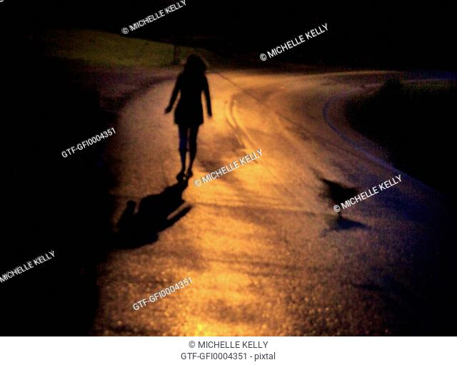 Girl alone on road at night time.backlit by headlights
