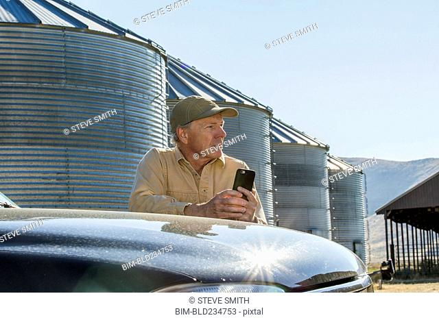 Caucasian farmer leaning on truck texting on cell phone