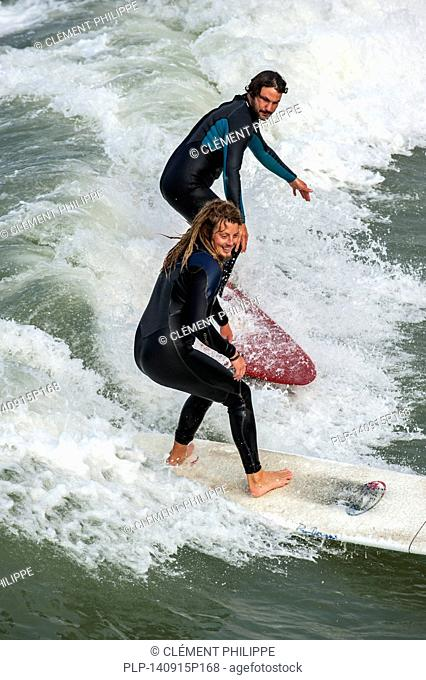 Two surfers in wetsuits riding wave on surfboard as it breaks at sea