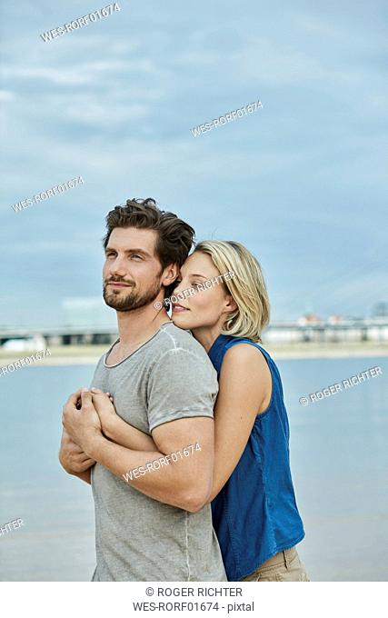 Affectionate young couple hugging at the riverbank