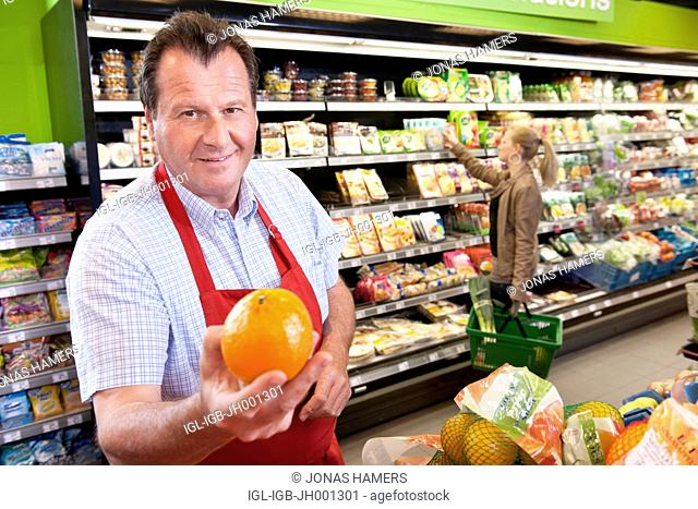 A supermarket employee arranges goods and food