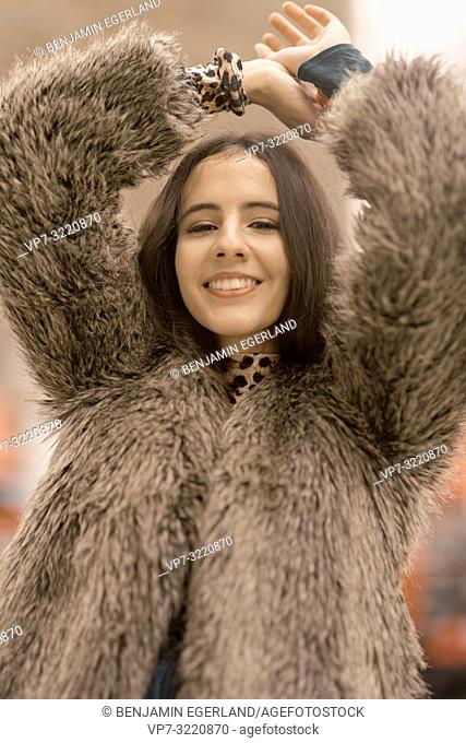 portrait of smiling woman wearing fashionable coat, in Munich, Germany