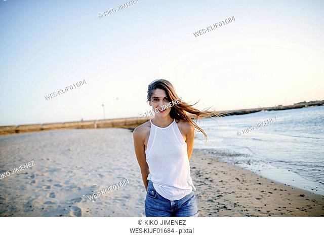 Portrait of young woman walking on the beach