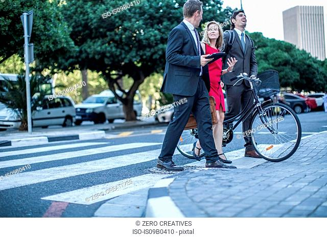 Businesswoman and male colleagues walking and talking in city