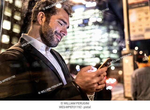 UK, London, businessman on the go checking his phone while commuting by night