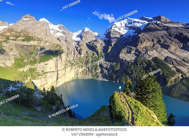 Hiker admires Lake Oeschinensee Bernese Oberland Kandersteg Canton of Bern Switzerland Europe
